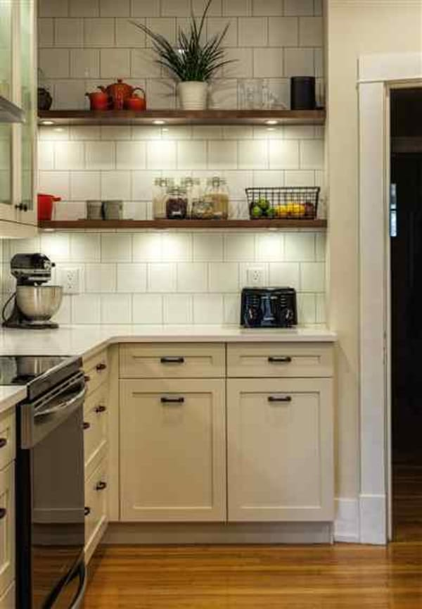 Gorgeous wood floating shelves with lighting warms up this kitchen in a previously dark corner.