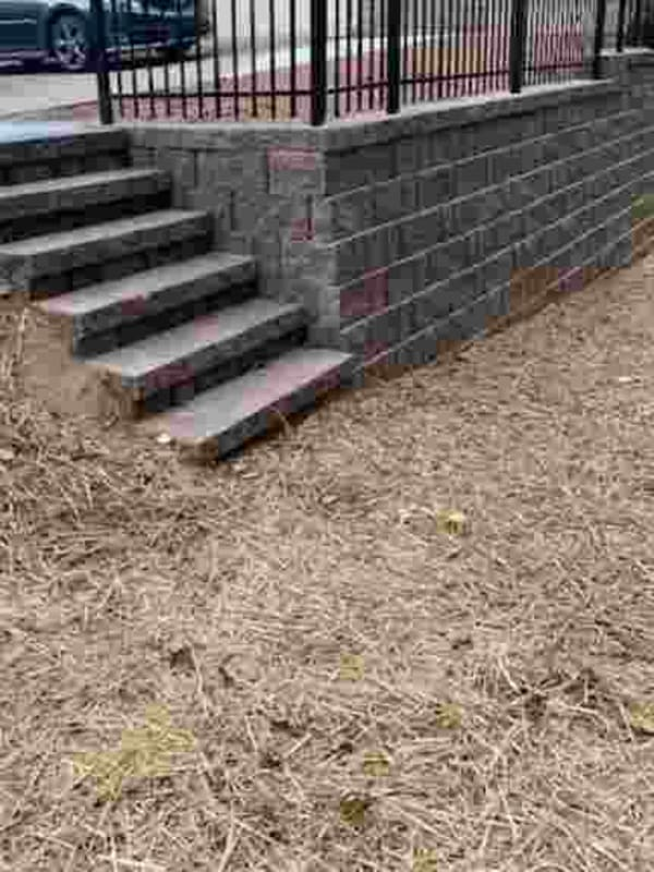Modular block retaining wall with steps and fencing.
