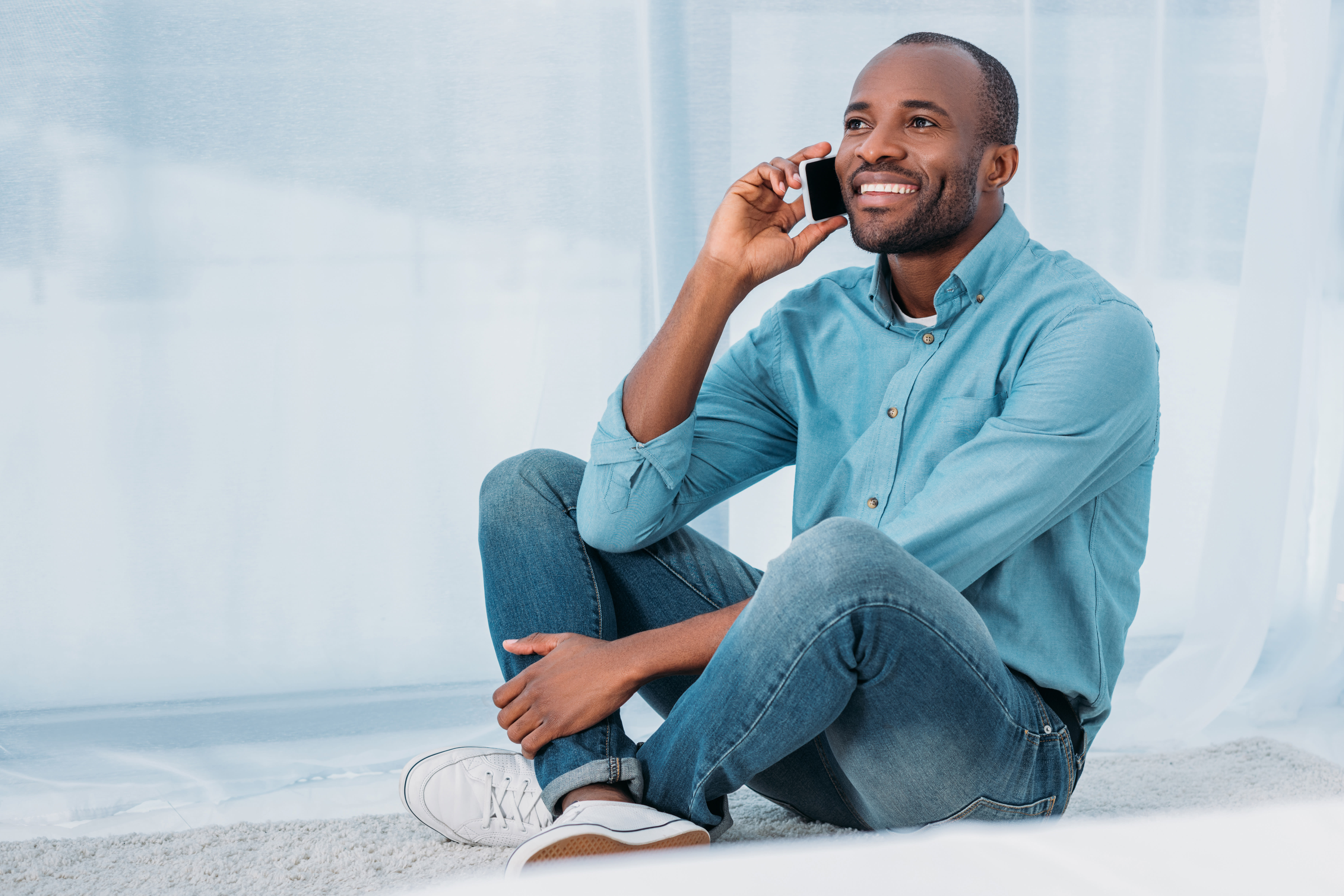 smiling african american man sitting on floor and talking by smartphone at home