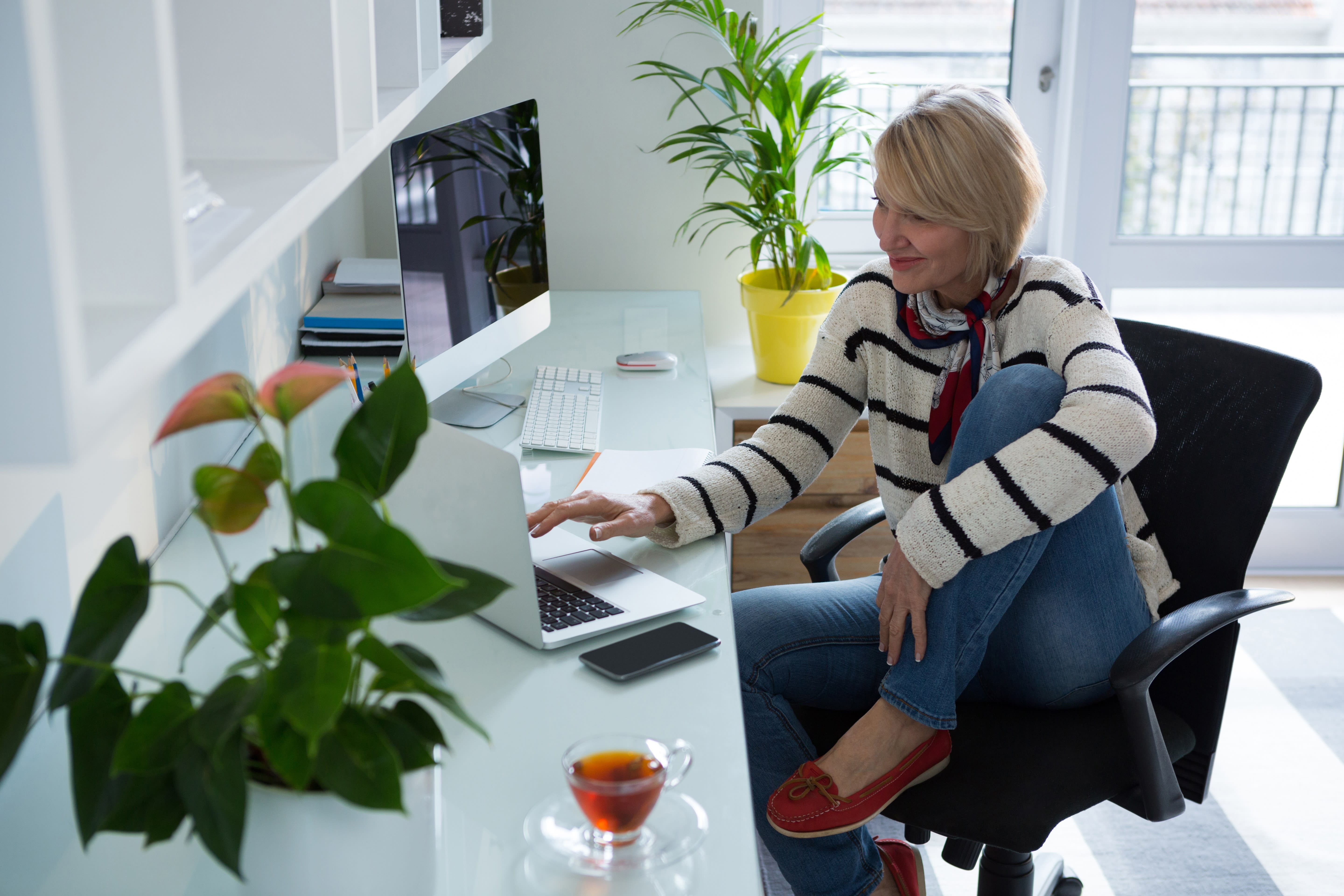 Blonde woman sitting in desk chair with one leg up working on laptop