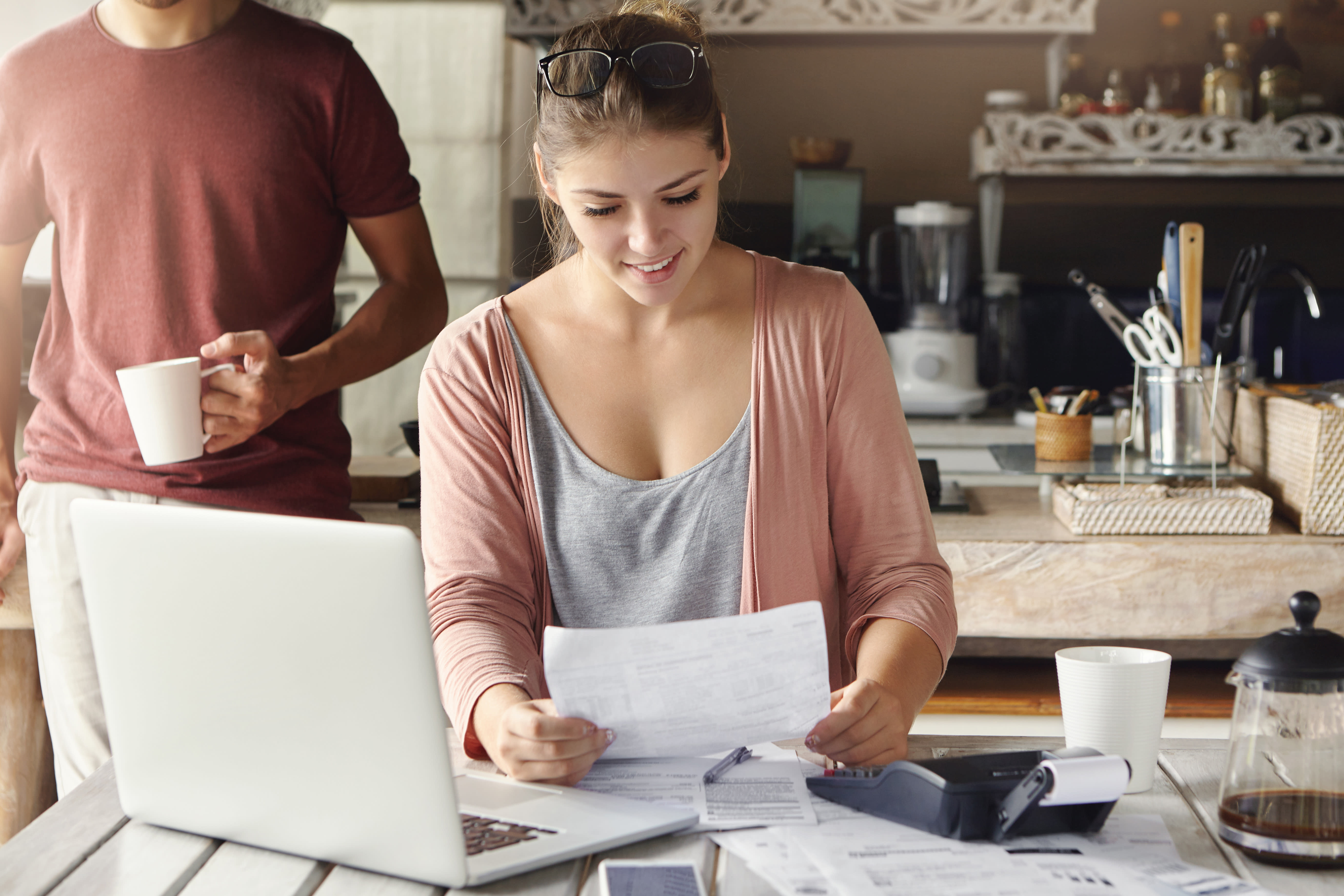 Woman on laptop working on taxes while her husband stands behind her