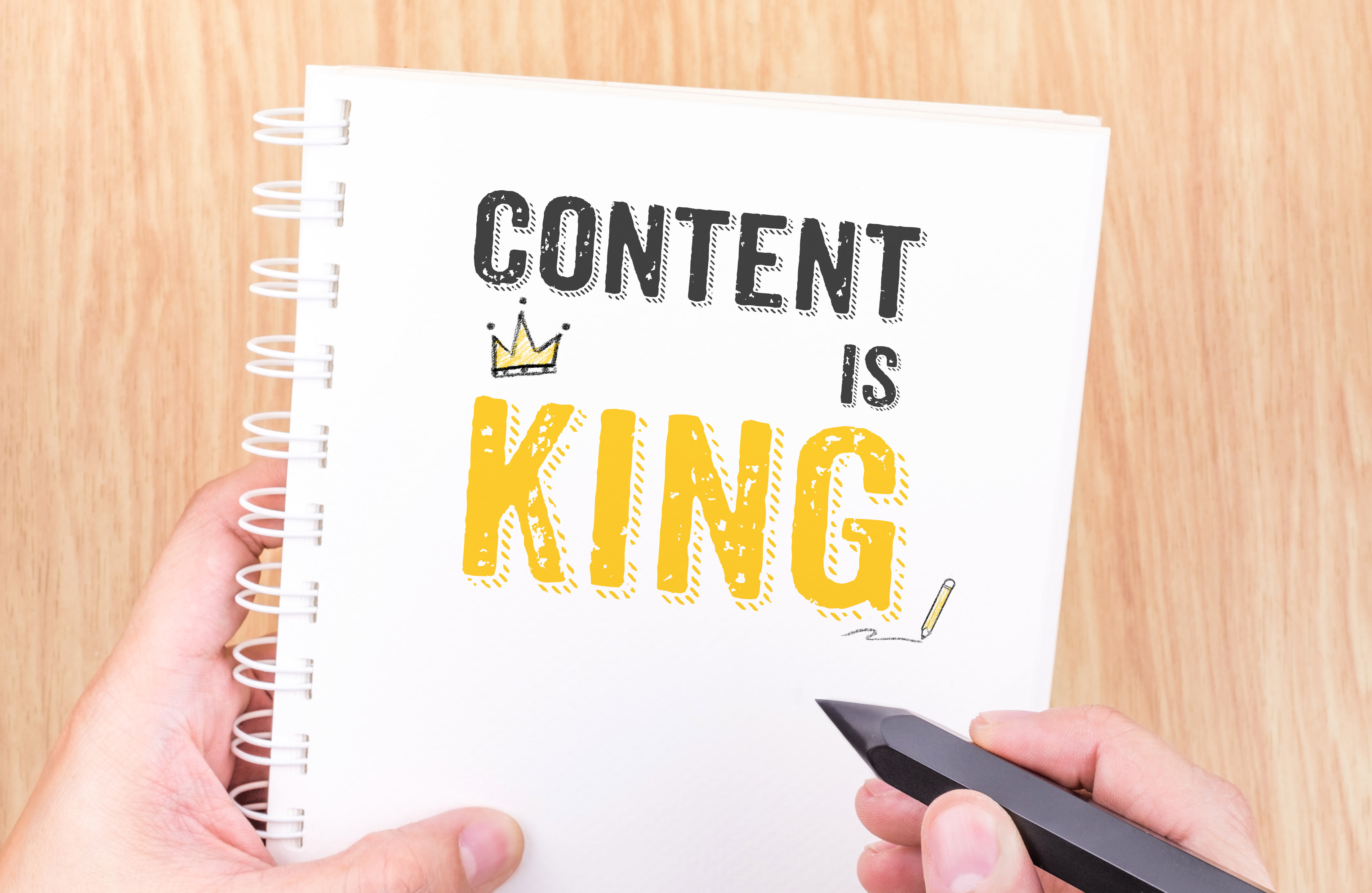 Content is King work on white ring binder notebook with hand holding pencil