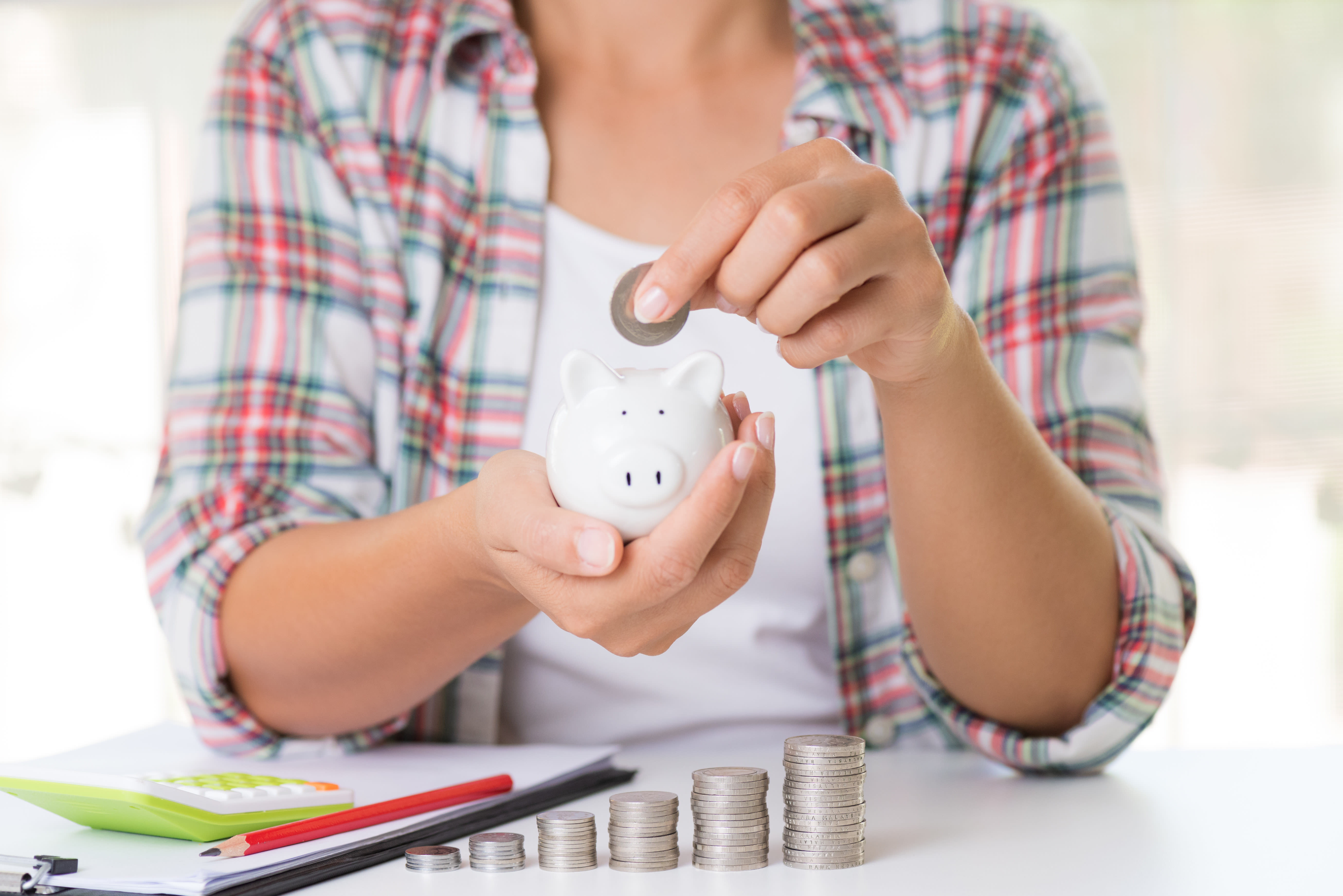 Woman hand putting money coin into piggy bank. Saving money wealth and financial concept.