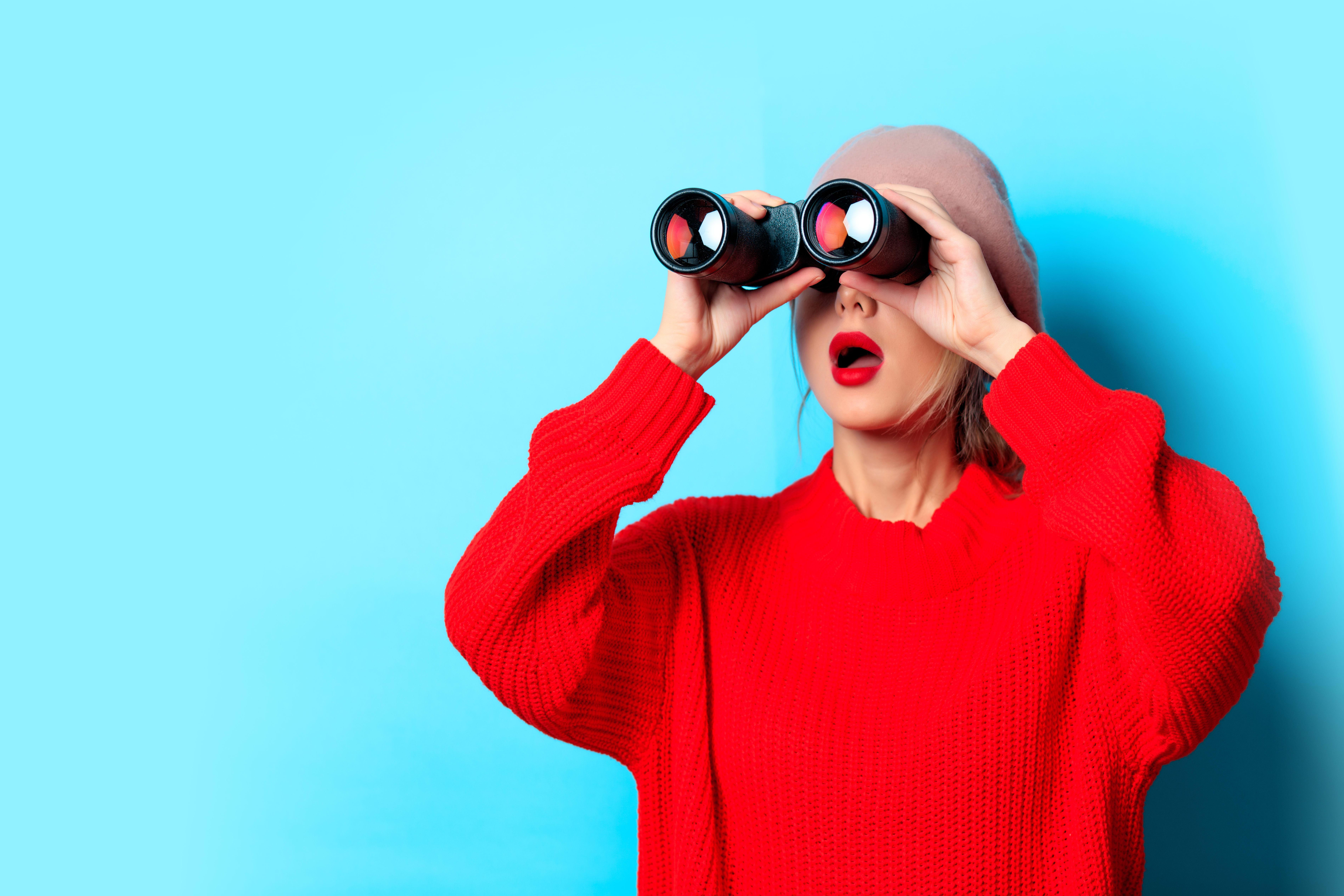 Woman in a big red sweater looking through binoculars