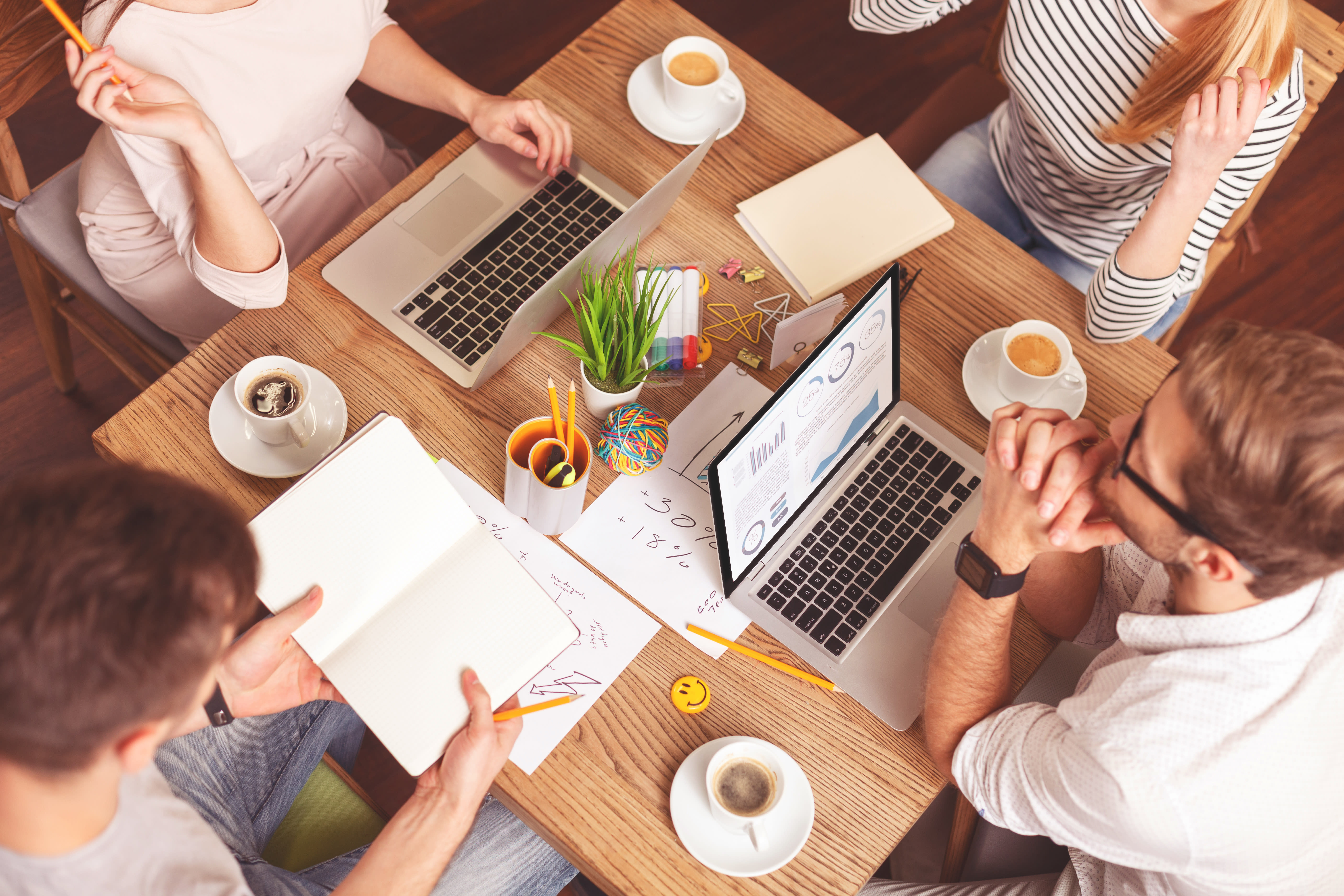 Four young professional adults working in coffee shop