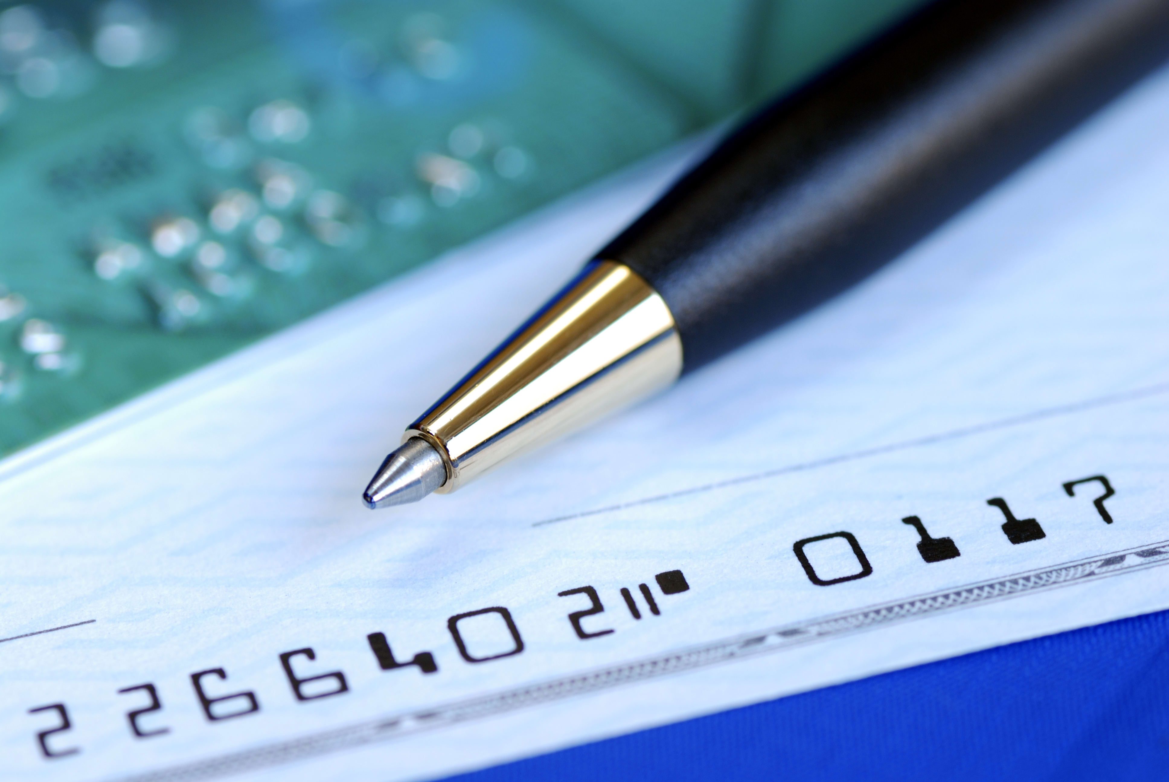 Close up of a pen on a check with a credit card