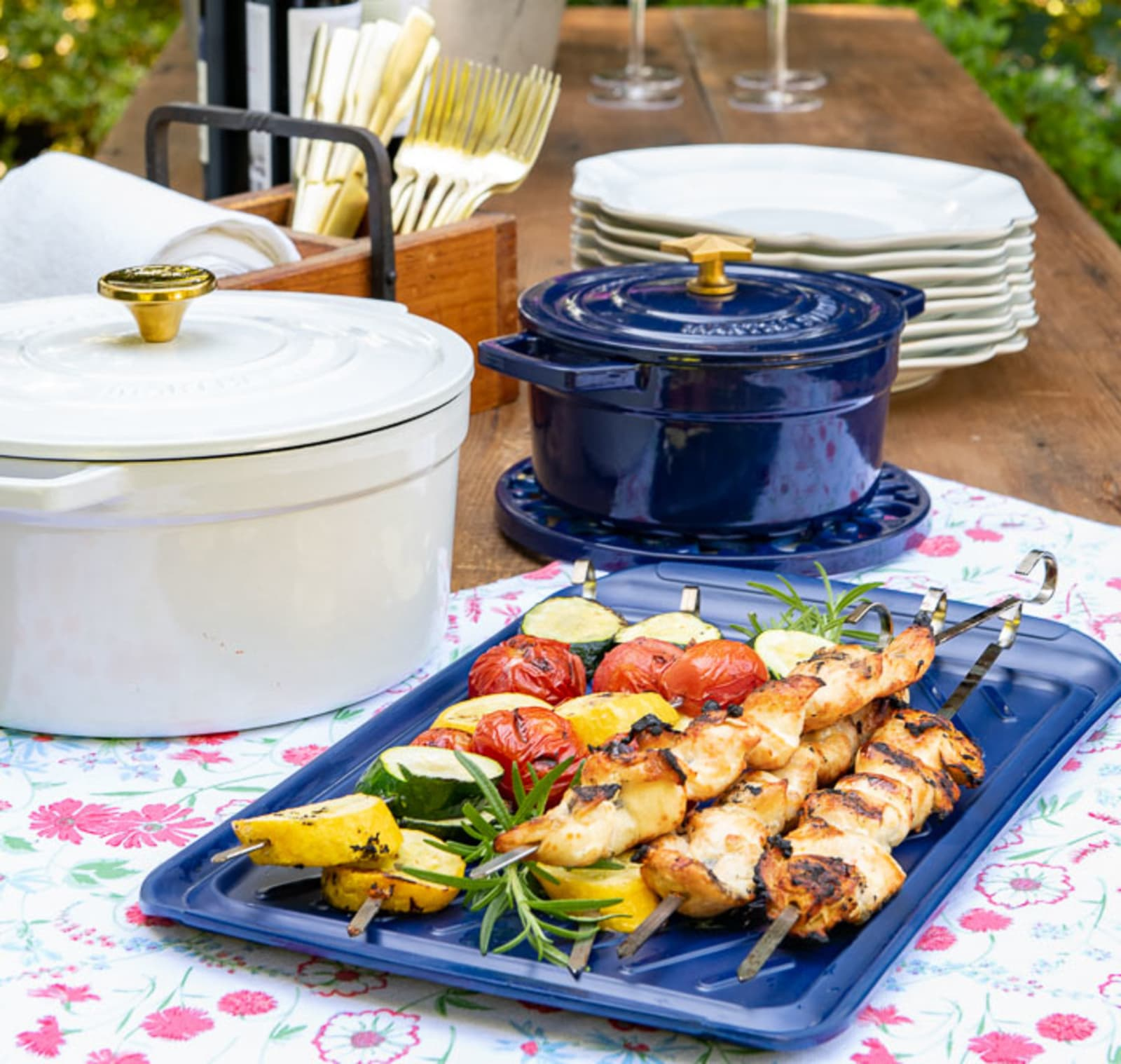 Outdoor table with chicken and vegetable skewers, wine, dinnerware, and flowers