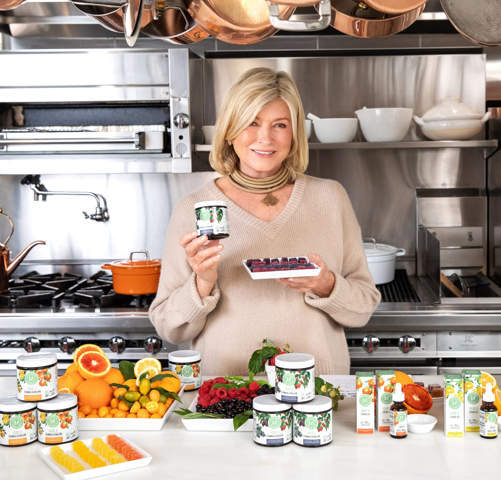 Martha Stewart in her kitchen holding a plate of CBD gummies