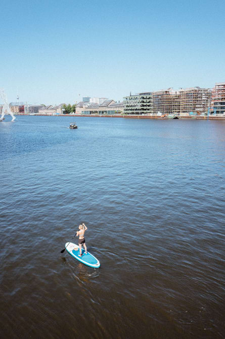 A woman on a stand up paddle on the Spree river