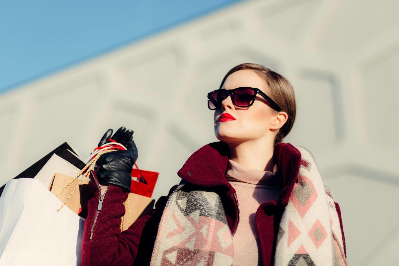 Frau mit Sonnenbrille und vielen Taschen