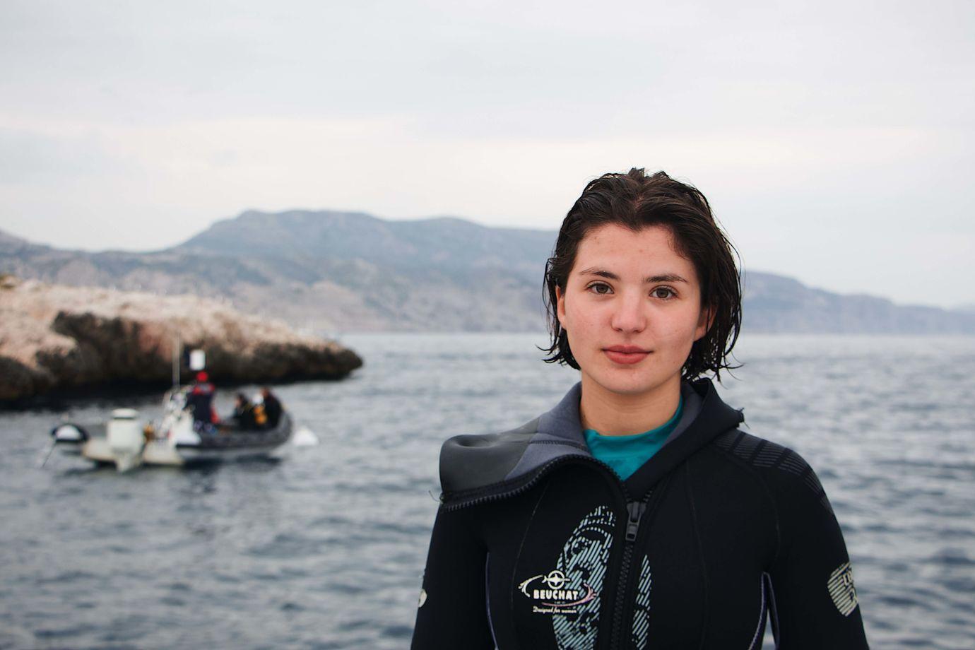 Frau im Neoprenanzug vor Meer