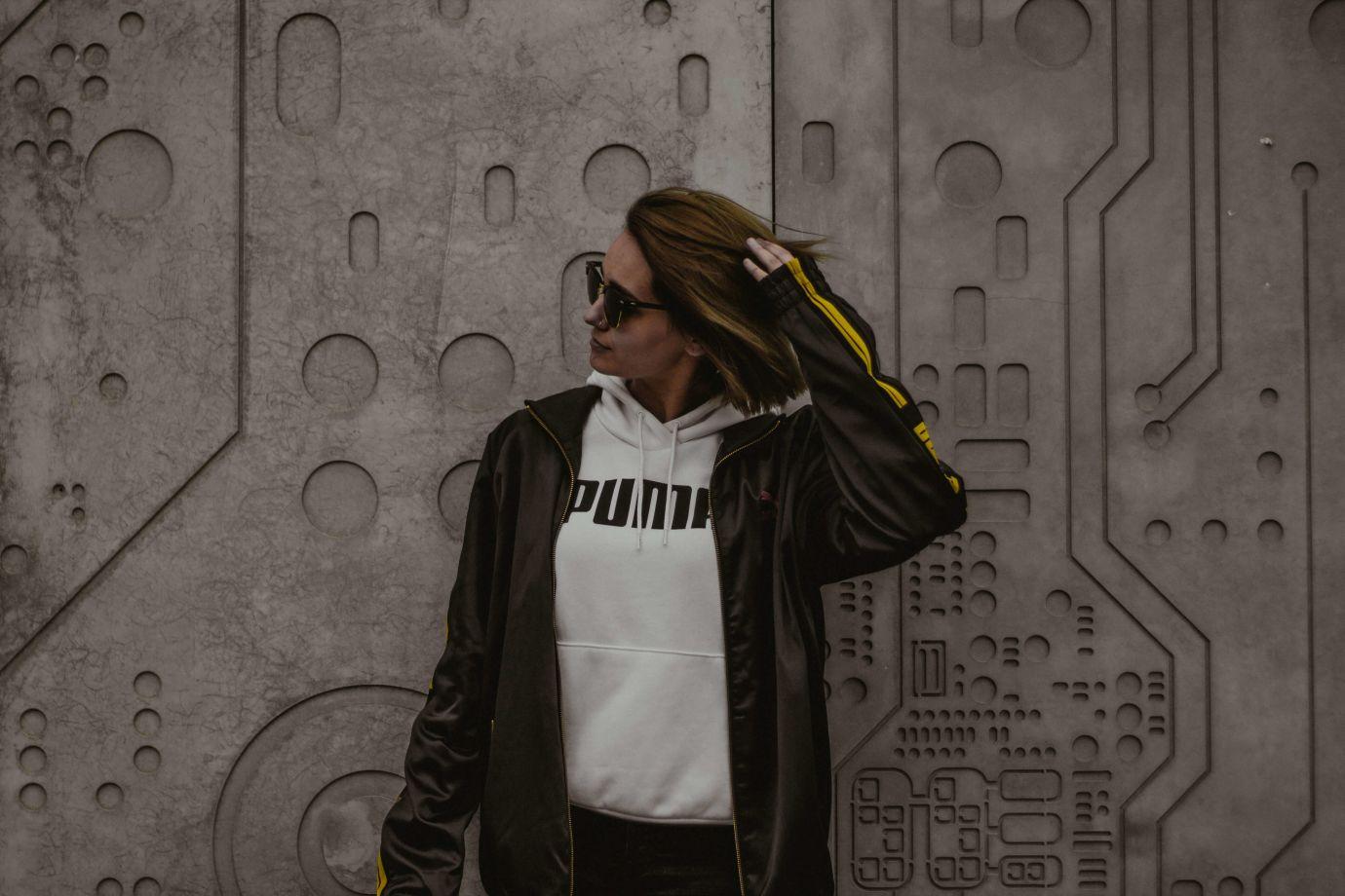 Frau im Puma Hoodie vor einer Wand