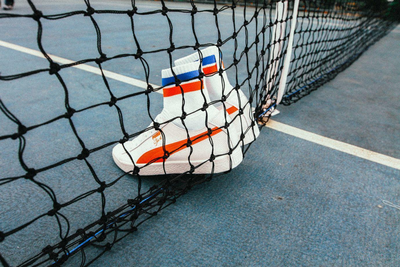 Puma Sneaker an ein Netz gelehnt