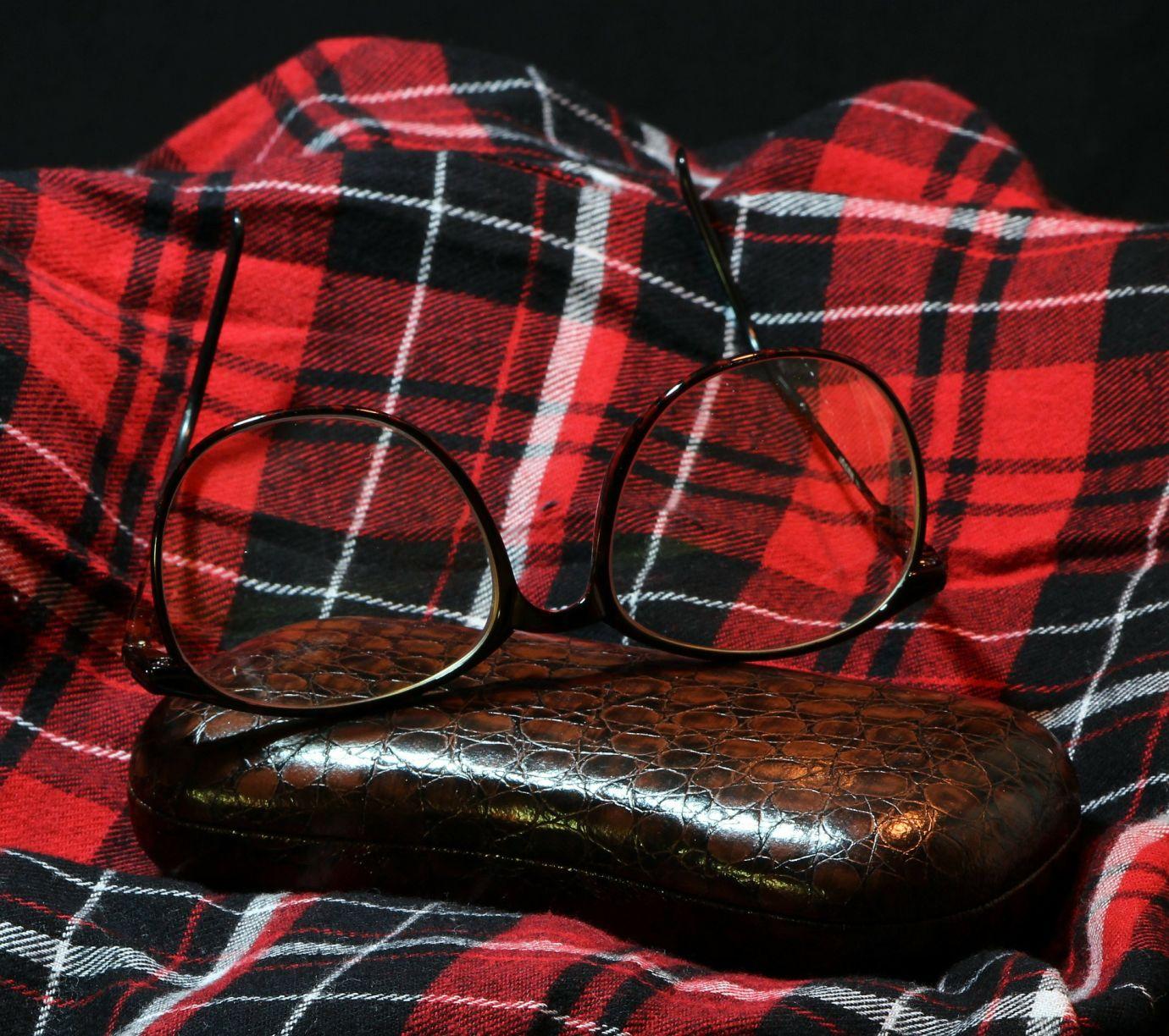 Brille mit Etui auf zusammengelegtem Flanellhemd
