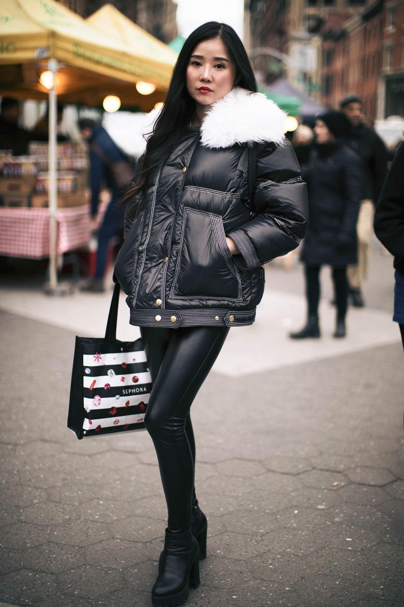 Frau in schwarzen Leggings und Daunenjacke auf Marktplatz