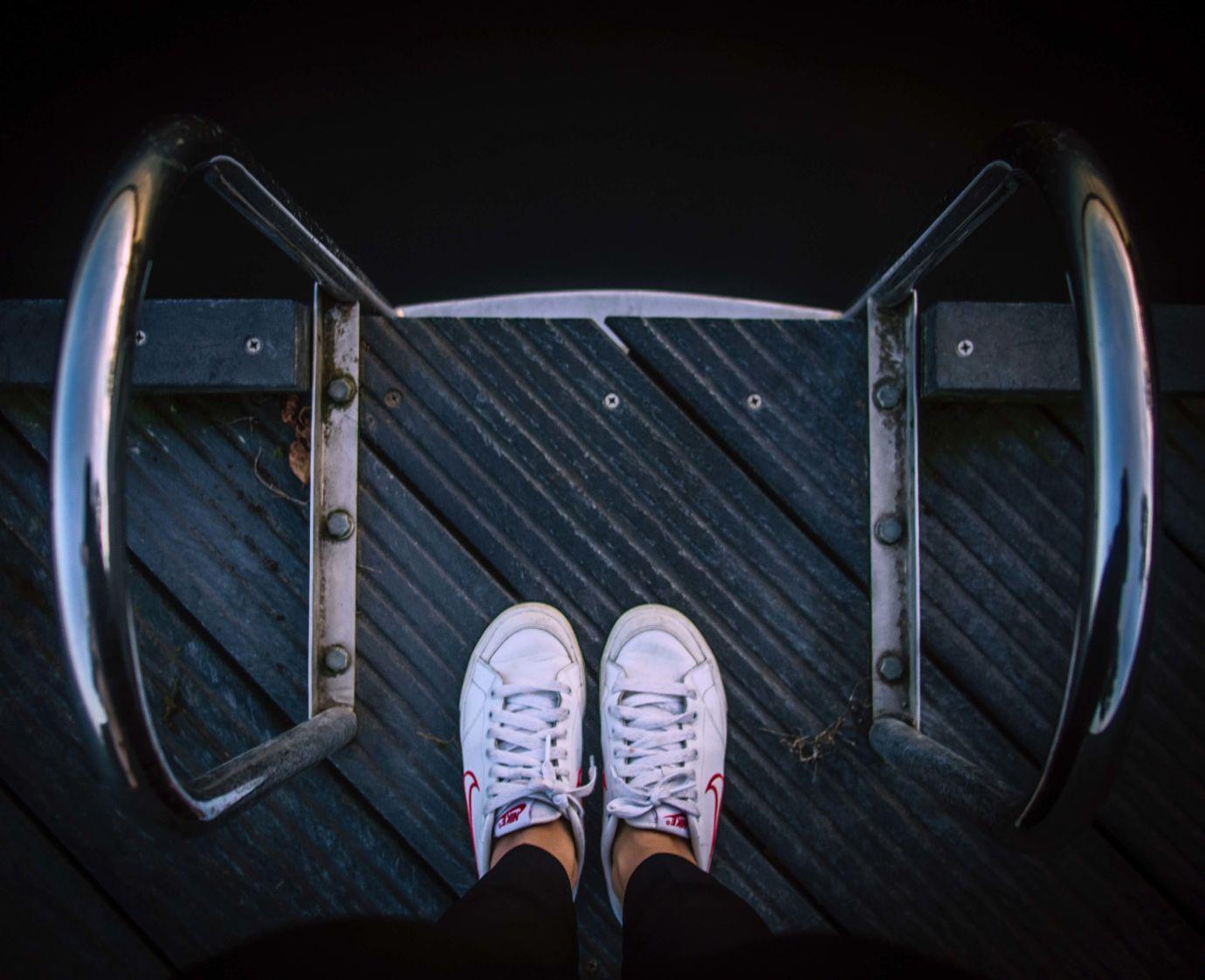 Blick hinab auf weiße Nike Sneaker und Geländer