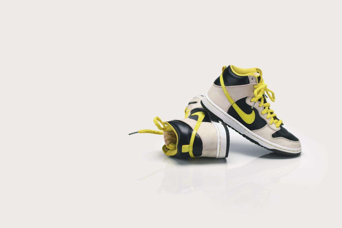 Schwarzweiße Sneaker mit gelben Schnürsenkeln und Nike Logo