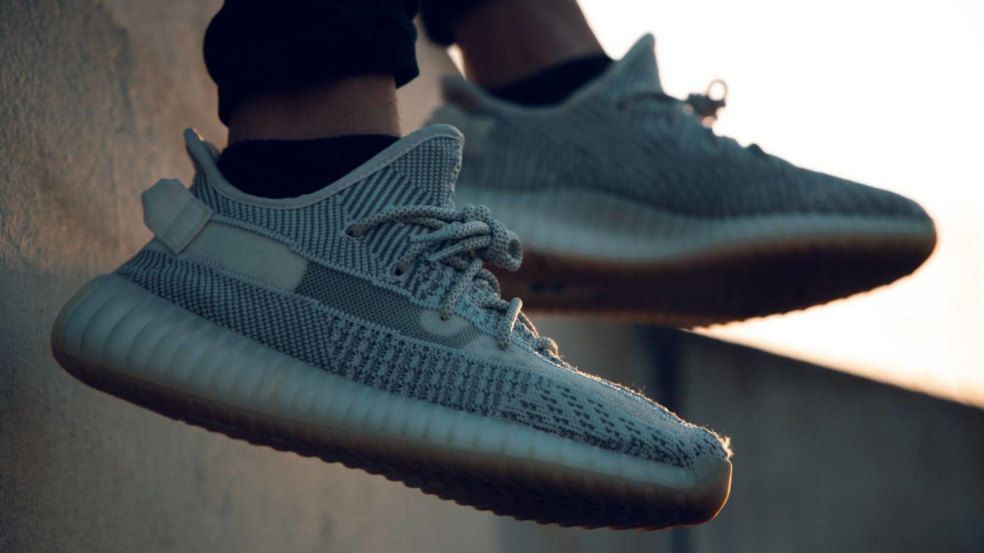 Füße in grauen Sneakern baumeln über Häuserkante