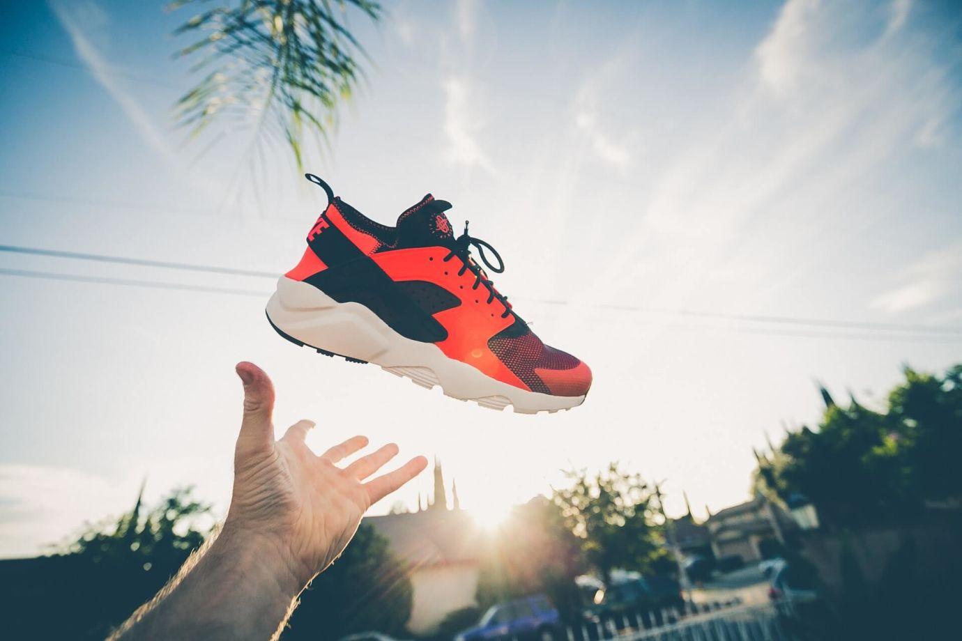 Rot-schwarzer Sneaker wird in die Luft geworfen