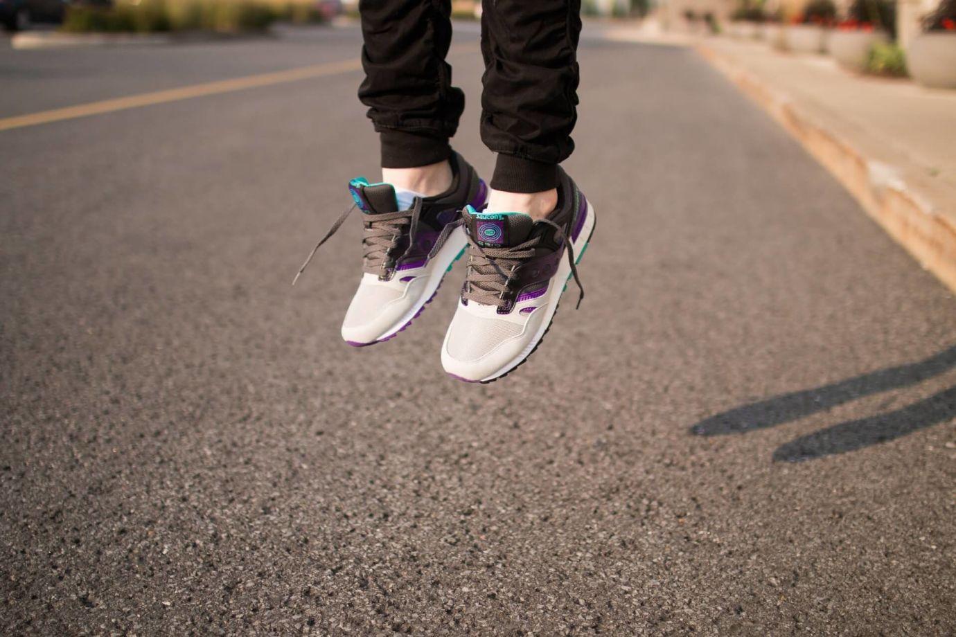 Person springt in braun-weißen Saucony Sneakern mit Lace Lock