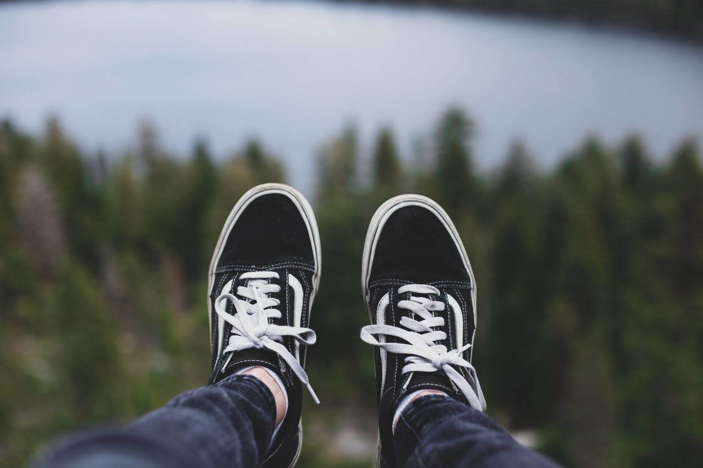 Schwarz-weiße Schuhe an Füßen vor Wald