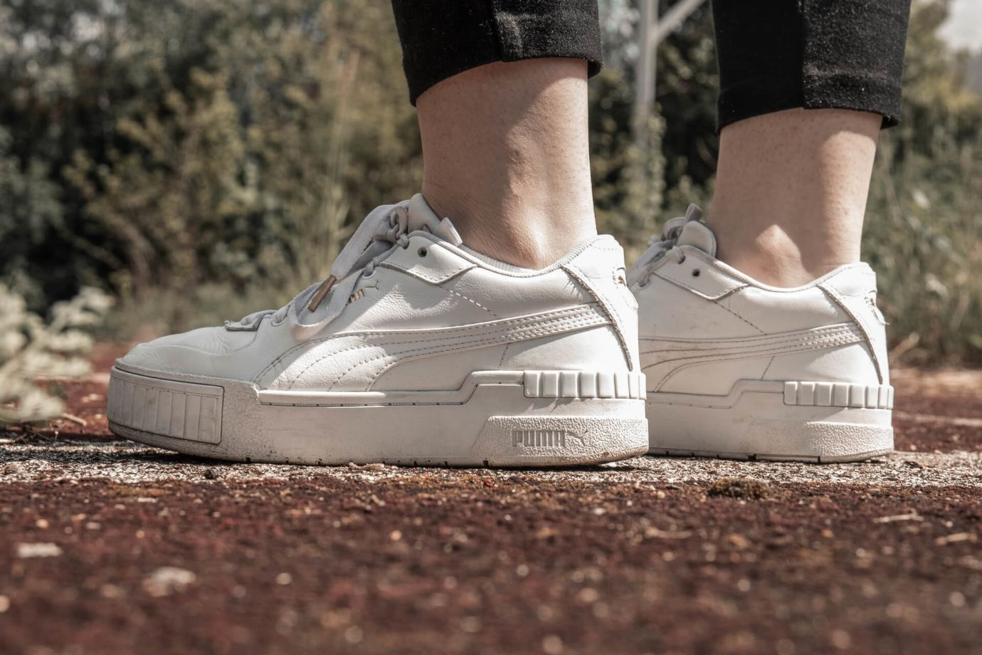 Weiße Puma Sneaker auf Straße