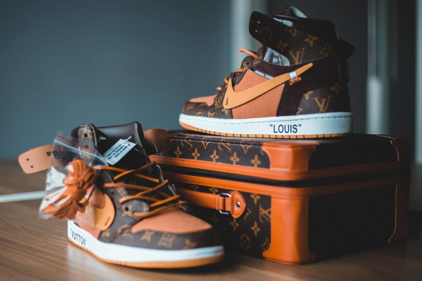 Orange-braune Louis Vuitton Sneaker auf kleinem Koffer