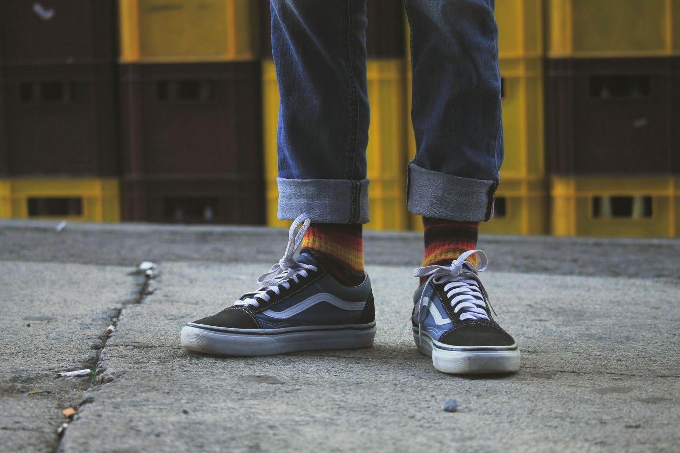 Person in Jeans trägt gestreifte Sneaker