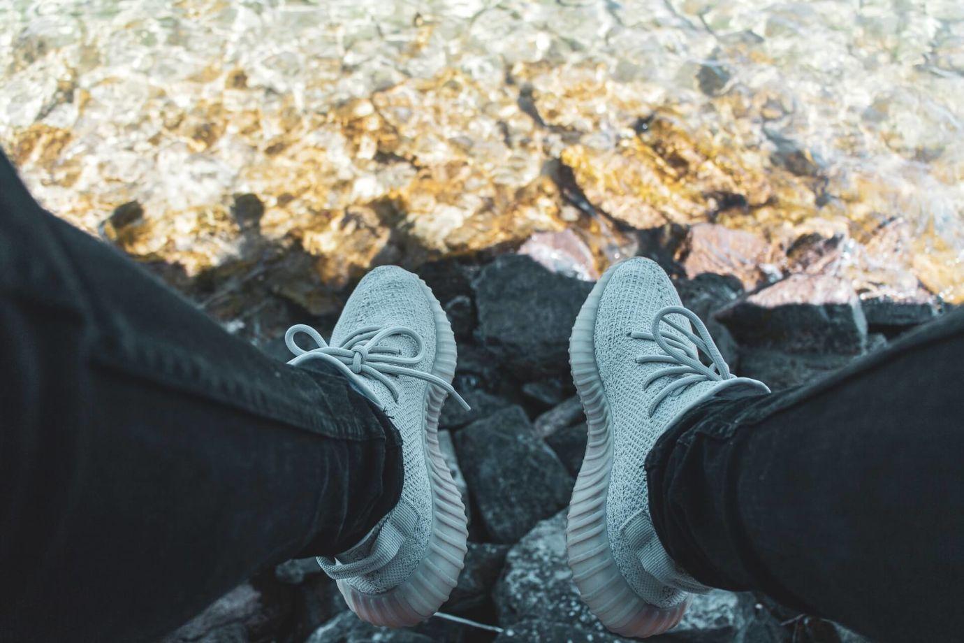 Blick auf Füße in weißen Yeezys