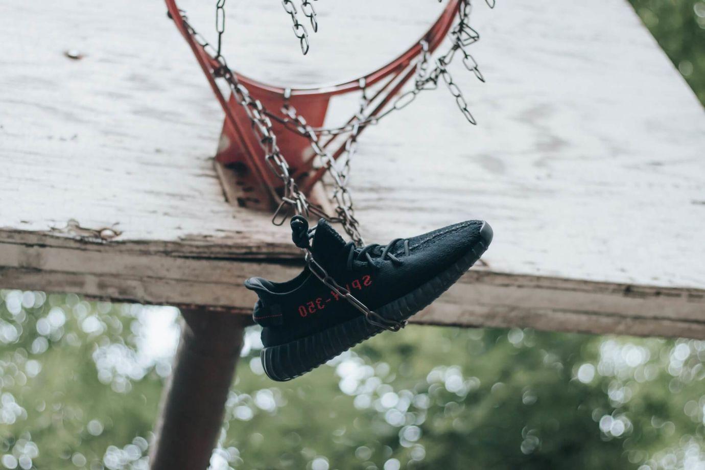 Schwarze Yeezys mit rotem Code Print hängen in Basketballnetz