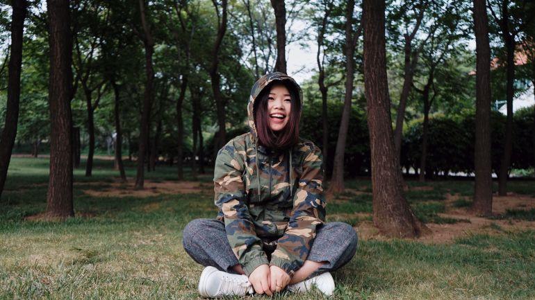 Junge Frau mit Jacke im Wald}