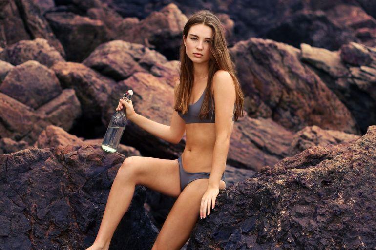 Frau in Bikini auf einem Felsen}