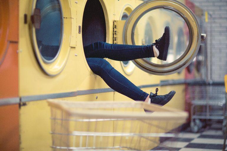 Person in der Waschmaschine lässt Beine herausbaumeln}