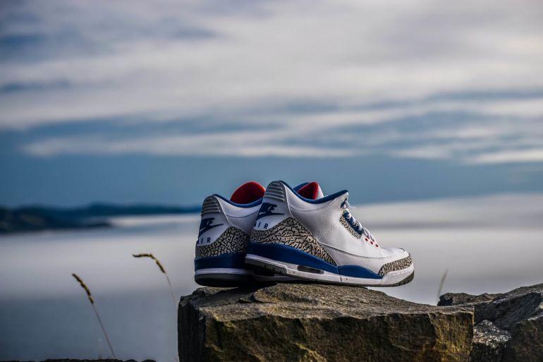 Weiße Nike Air Sneaker auf Stein am Meer}
