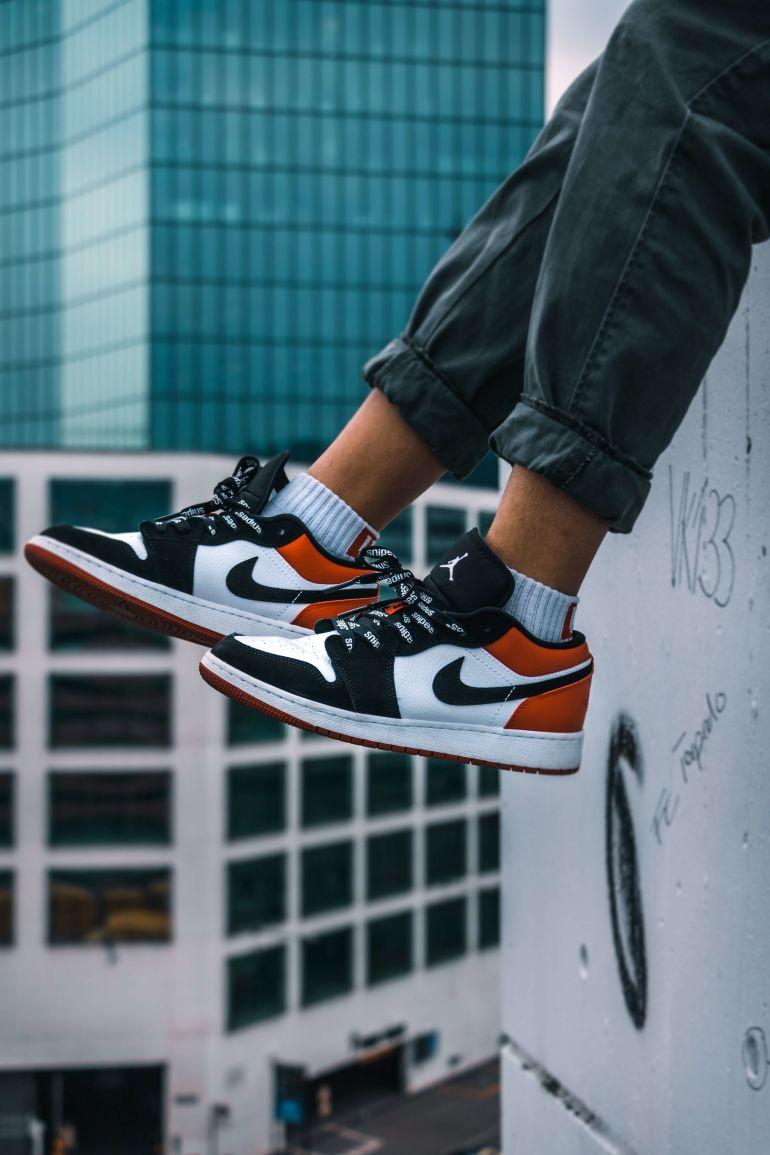 Nike Sneaker baumeln über Dachkante