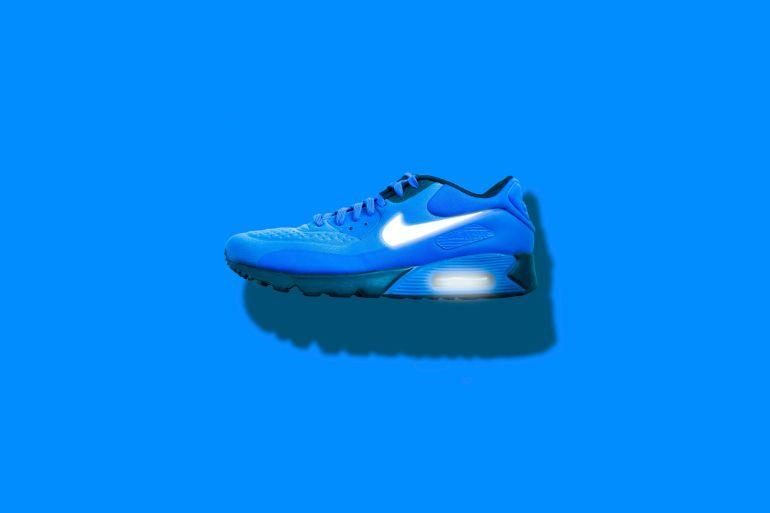 Blauer Nike Sneaker vor blauem Hintergrund mit leuchtend weißem Logo