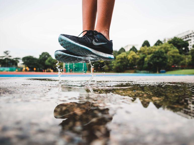 Sprung in Pfütze mit schwarz-weißen Nike Sneakern