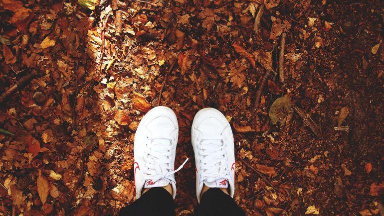 Blick hinab auf weiße Nike Sneaker und Laub
