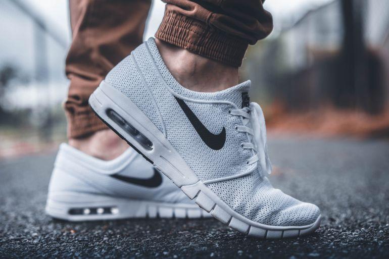Mann in weißen Nike Sneakern mit schwarzem Logo