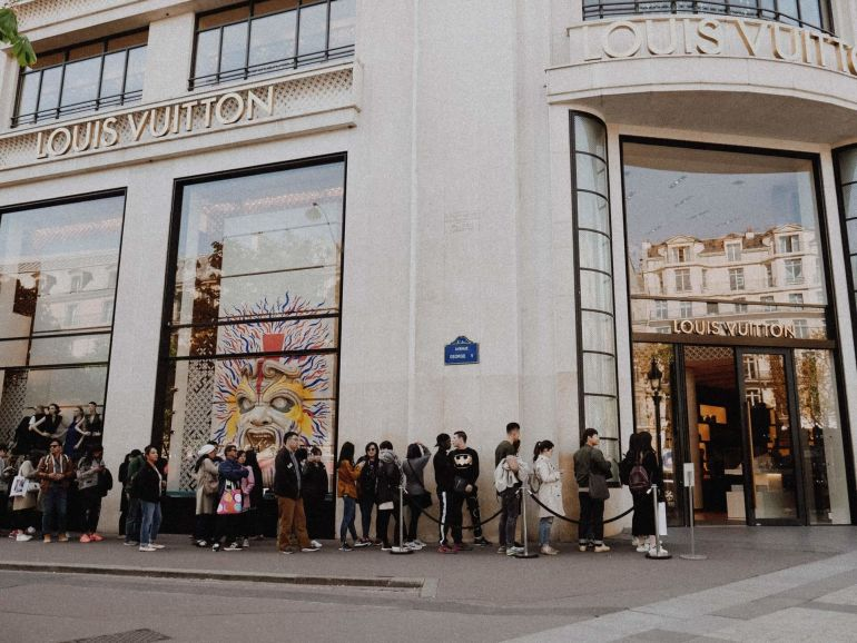 Kunden warten in Schlange vor Louis Vuitton Store}