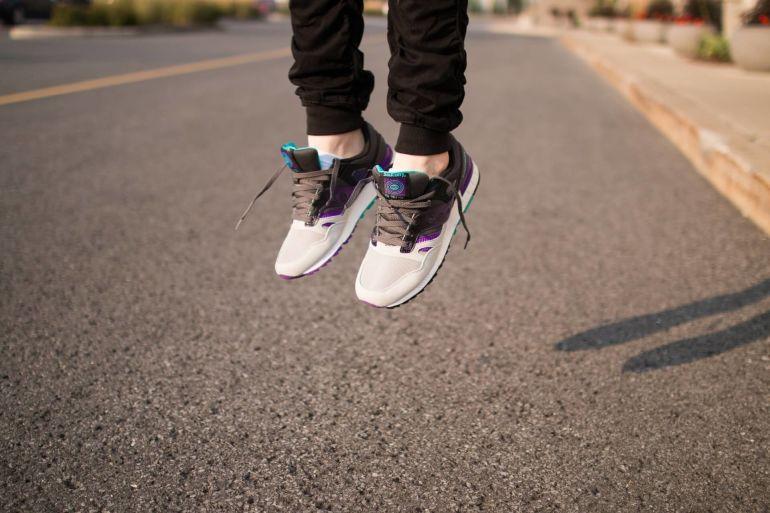 Person springt in braun-weißen Saucony Sneakern mit Lace Lock}