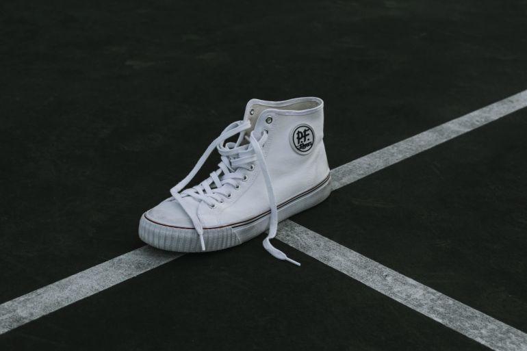 Weißer P.F. Flyers Schuh auf Straße