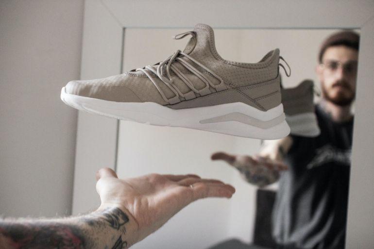 Mann hält beige-weiße Sneaker vor Spiegel}