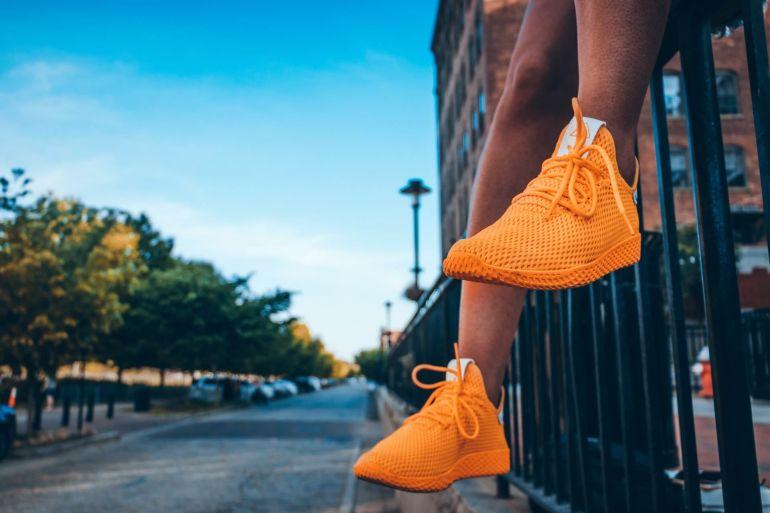 Person in orangenen Sneakern sitzt auf Geländer}