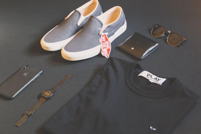 Hellblaue Vans, Sonnenbrille, schwarzes, zusammengefaltetes Shirt und andere Gegenstände}
