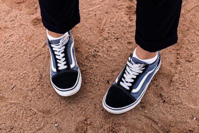 Person trägt blau-weiß-schwarze Schuhe mit Deadstock}
