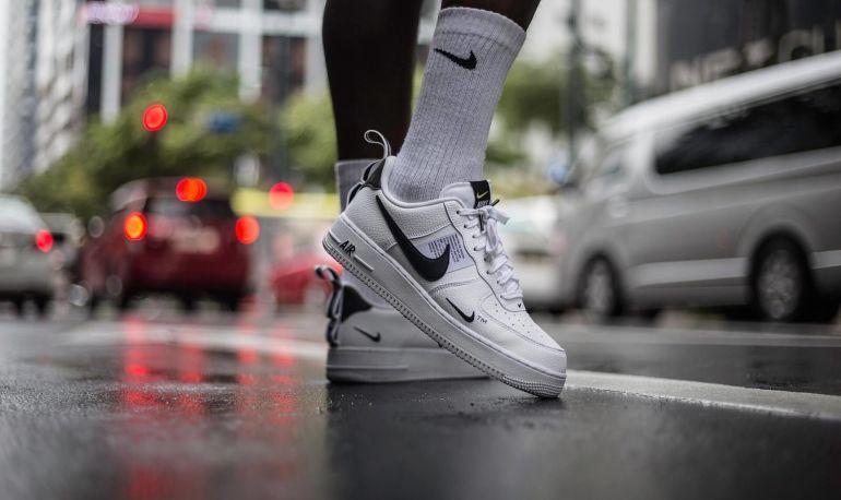 Person in weißen Nike Air überquert Straße in Stadt}