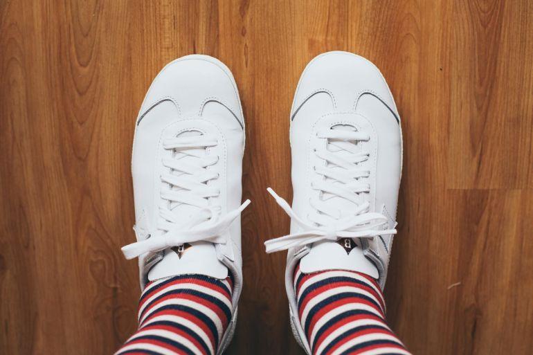 Blick hinab auf weiße Sneaker und gestreifte Socken}