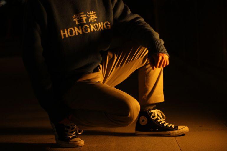 Mann mit Hong Kong Pullover trägt dunke Converse Allstar Schuhe}