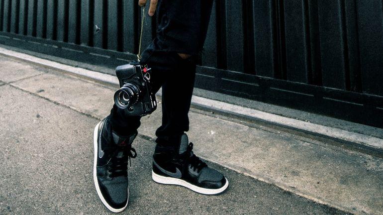 Mann mit Kamera in schwarzen Nike Sneakern